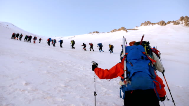 alpine climber is watching the team climbing  in the peak of mountain in winter - esplorazione video stock e b–roll