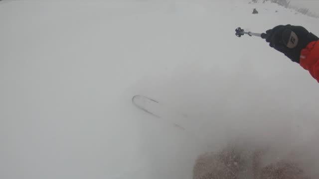 vídeos de stock e filmes b-roll de pov of alpine skier descending powder slope in slow motion - bastão de esqui