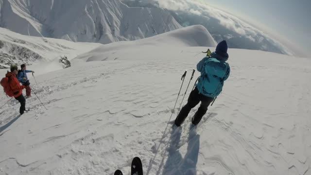 POV of alpine skier descending powder slope