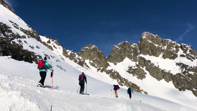Alpine skiers ascend towards a ridge during alpine touring off piste at La Flegere ski resort on February 24 2018 near ChamonixMontBlanc France The...