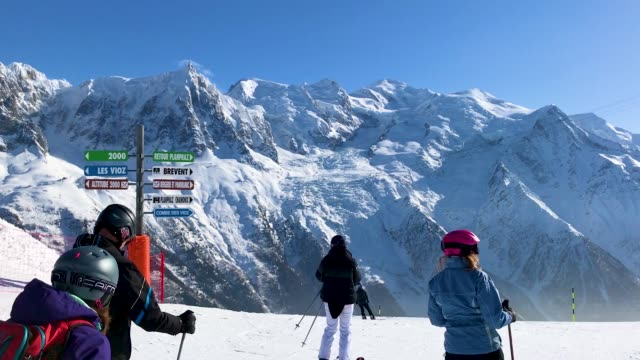 Alpine skiers prepare to descend on a piste at Le Brevent ski resort on February 24 2018 near ChamonixMontBlanc France The French Alps are a popular...