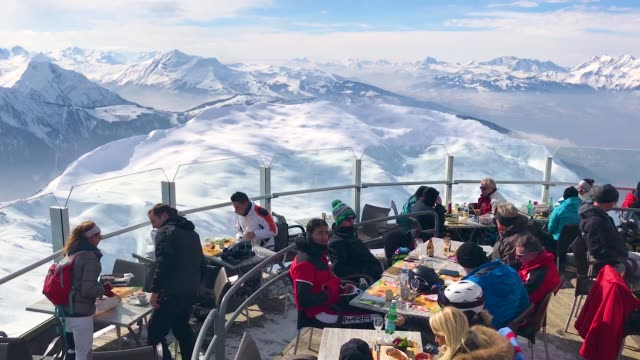 Alpine skiers relax at a panorama restaurant in the sun at the Brevent summit on February 23 2018 near ChamonixMontBlanc France The French Alps are a...