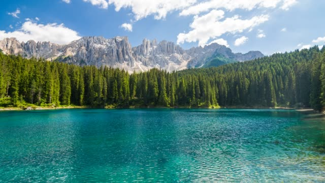 alpine turquoise carezza lake with latemar mountain range in background, trentino in dolomites, italy - lago video stock e b–roll