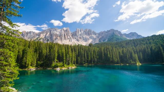 alpine turquoise carezza lake with latemar mountain range in background - dolomites stock videos & royalty-free footage