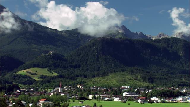 ws zi alpine village and ehrenberg castle ruins on top of mountain covered with clouds, tyrol, austria - österreichische kultur stock-videos und b-roll-filmmaterial