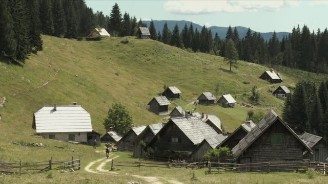 ws alpine village zajamniki, two cyclist in distance, bohinj, triglav national park, slovenia - triglav national park stock videos and b-roll footage