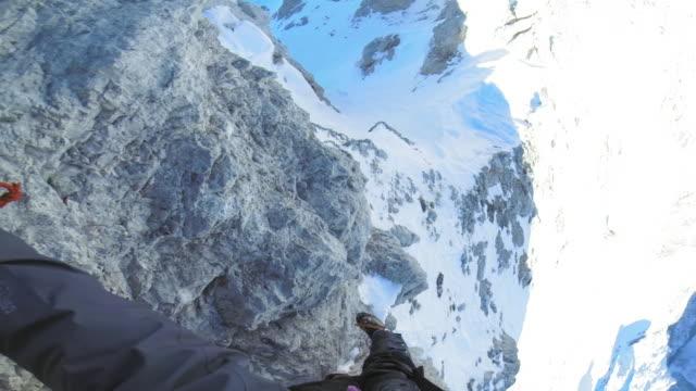 vidéos et rushes de pov alpiniste grimpant au sommet de la montagne en hiver - caméra portable