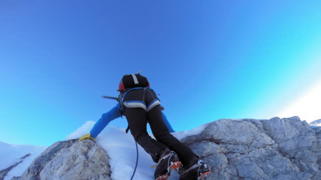 POV Alpinist climbing on the snowy mountain
