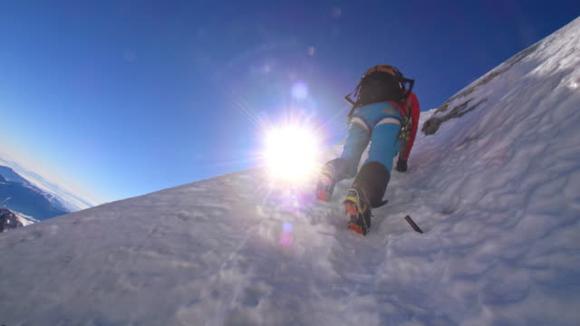 alpinist climbing up the steep snowy wall in sunshine - climbing wall stock videos & royalty-free footage