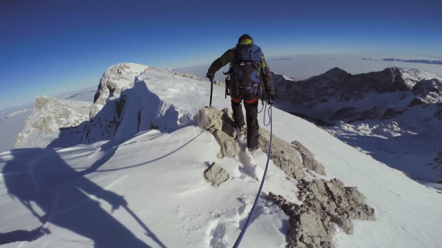 POV Alpinists tied together as they walk on a snowy peak