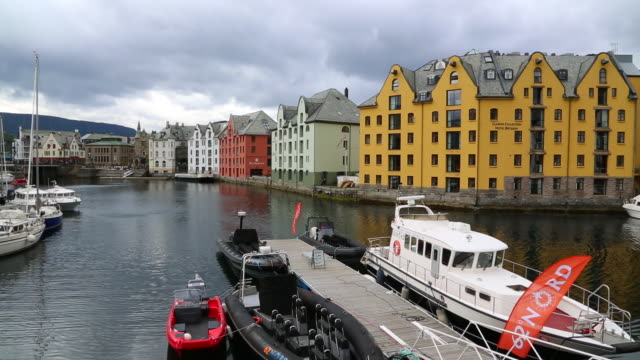 alseund, the canal to the inner harbor, and art nouveau buildings - norvegia video stock e b–roll