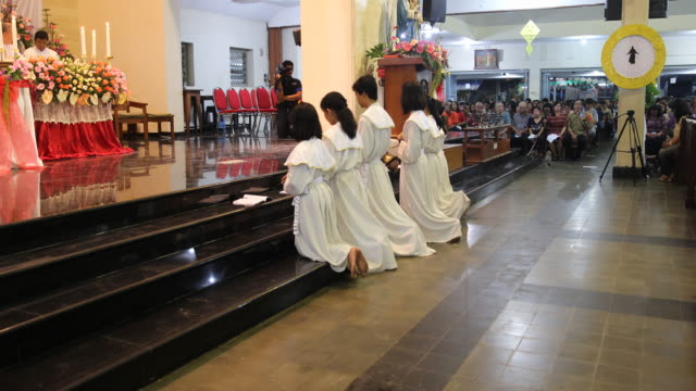 altar server and praying believers during the the eucharist in a worship in a very colorful catholic church in yogyakarta in java in indonesia - indonesian ethnicity stock videos & royalty-free footage