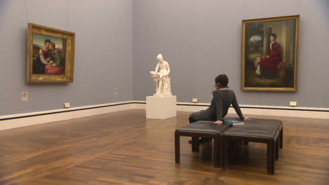 alte pinakothek, indoor, art, people, paintings and sculpture, woman sitting on chair and looks at paintings - museum stock videos & royalty-free footage