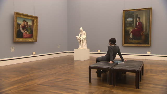 alte pinakothek, indoor, art, people, paintings and sculpture, woman sitting on chair and looks at paintings - kunst und handwerksmaterial stock-videos und b-roll-filmmaterial