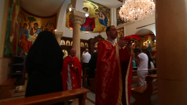 Alter boy and priests bring gifts to alter pass by church members and nun during Mass at Melkite Greek Catholic Church in Lebanon
