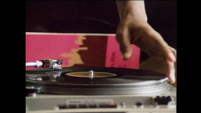 stockvideo's en b-roll-footage met cu alternating pan of dj's hands scratching records; 1984 - draaitafel