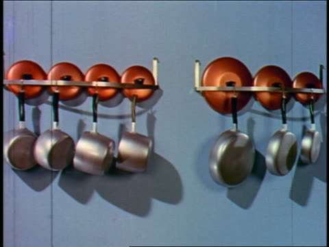 1955 aluminum pots with lids hanging on racks on blue wall - lid stock videos and b-roll footage