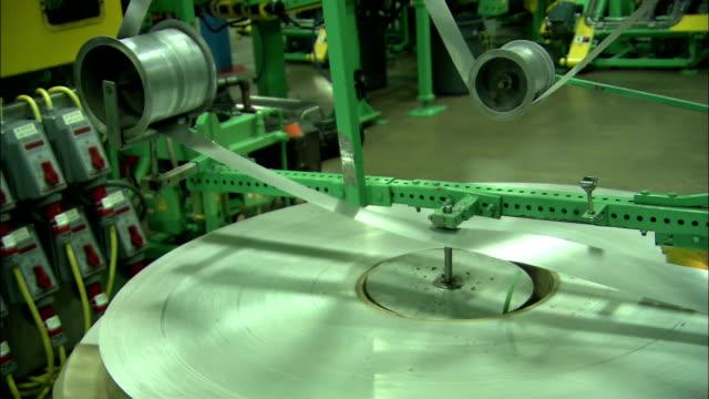 aluminum ribbon winds through pulleys in a factory. - ausgefranst stock-videos und b-roll-filmmaterial