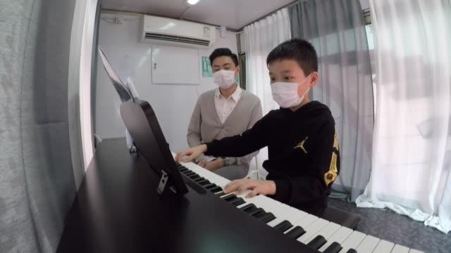 alumnos de una escuela de música de hong kong toman sus clases en el camino con la ayuda de un camión - música stock videos & royalty-free footage