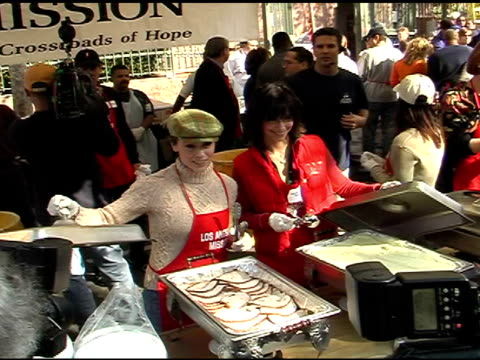 alyssa milano and jennifer love hewitt at the celebrities reach out to homeless at los angeles mission in los angeles california on november 26 2003 - alyssa milano stock-videos und b-roll-filmmaterial