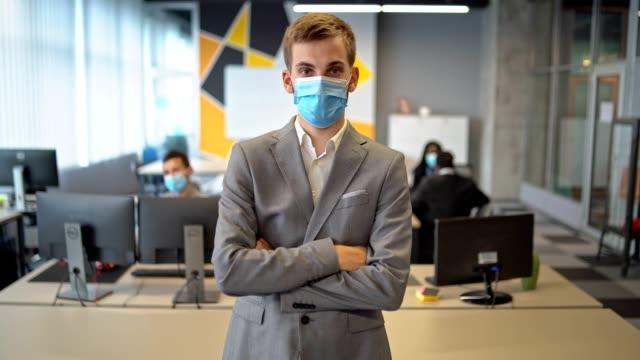 jag kommer att vinna - självsäker affärsman bär skyddande mask sand på sitt kontor och titta in på kameran - människoarm bildbanksvideor och videomaterial från bakom kulisserna
