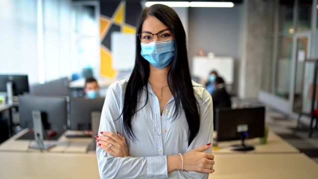 i am going to win - self confident businesswoman wearing protective mask sands in her office and watching in to the camera - human limb stock videos & royalty-free footage