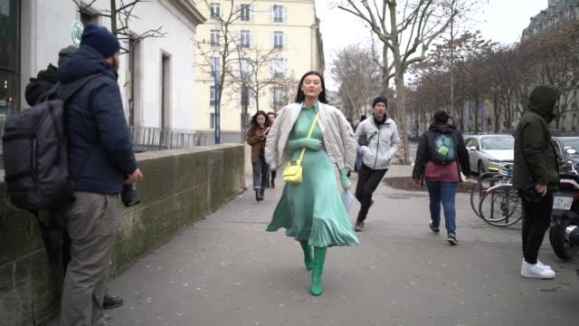Amalie Gassmann wears a green silk dress a white bomber jacket a yellow bag green boots outside Acne during Paris Fashion Week Menswear F/W 20192020...