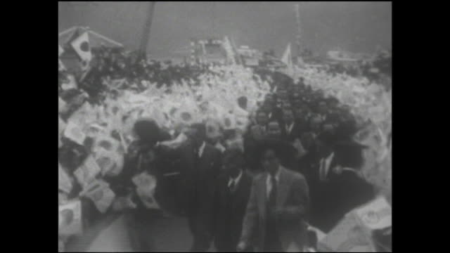 Amami Oshima islanders wave Japanese flags as the Governor of Kagoshima and his entourage arrive to celebrate the return of Japanese rule.