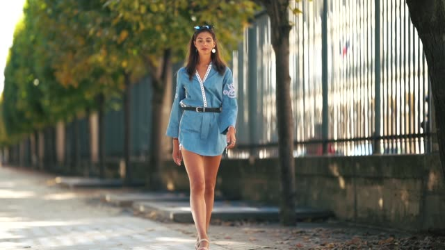 amanda derhy wears a blue denim dress with white embroidery from l'atelier d, zara white shorts, pull & bear sneakers shoes, on september 8, 2018 in... - 背が高い点の映像素材/bロール