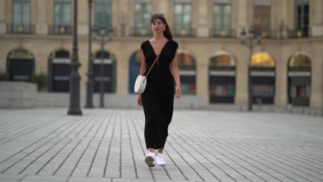 amanda derhy wears earrings a black lowneck vneck dress a white circular round straw summer bag a watch white adidas sneakers shoes on august 09 2020... - v neck stock videos & royalty-free footage