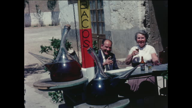 Amateur home movie footage featuring two British tourists enjoying drinks at a local tapas bar in the Spanish seaside town of Sitges circa August 1958