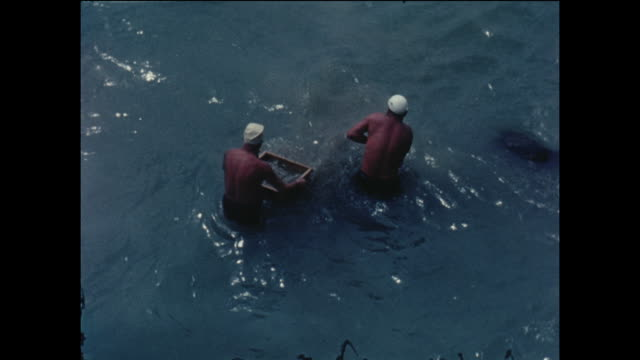 Amateur home movie footage featuring two local men panning in the sea at the Spanish coastal town of Sitges circa August 1958