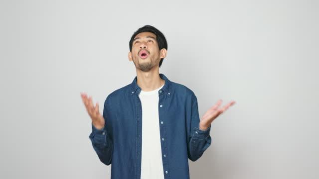 stockvideo's en b-roll-footage met verbaasde aziatische man geschokt, zeggen omg. portret van knappe aziatische kerel die terwijl het bevinden over grijze achtergrond, 4kresolutie wordt verrast - mond open