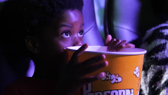 amazed young african american girl in movie theatre holding popcorn, close up - film industry stock videos & royalty-free footage