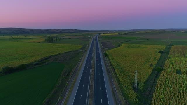 amazing aerial view drone flying over highway after sunset - country road stock videos & royalty-free footage