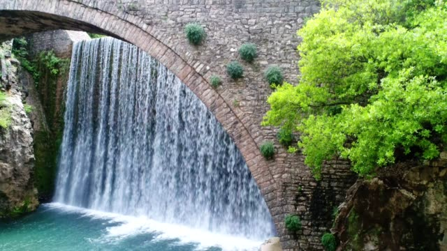 Amazing aerial view of a majestic waterfall and an ancient Roman bridge, famous places in Greece, travel destinations,