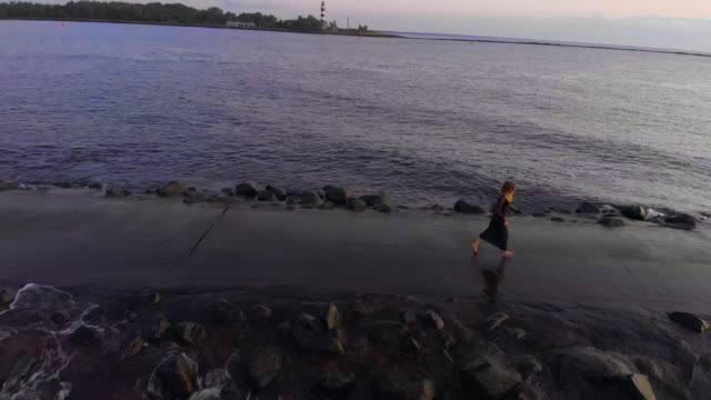 amazing aerial view of young running woman along rocky pier and beautiful waves of baltic sea gulf - endast unga kvinnor bildbanksvideor och videomaterial från bakom kulisserna
