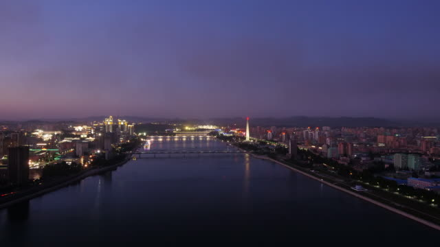 amazing day to night shot of skyline of pyongyang north korea, drpk. wide shot from above. sunset with juche tower, taedong river, may day stadium - spoonfilm stock videos and b-roll footage