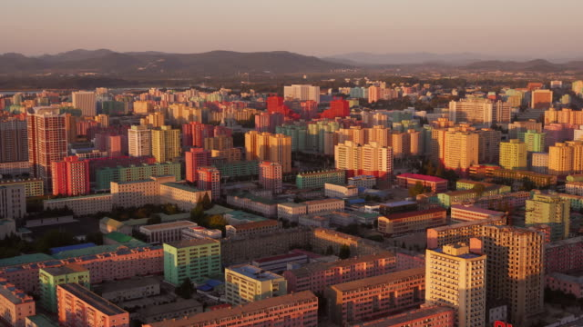 amazing day to night time-lapse of the colorful houses around the workers monument in pyongyang, north korea, drpk. wide shot from juche tower above - north korea stock videos & royalty-free footage