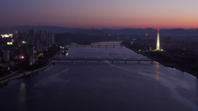 amazing night to day shot of skyline of pyongyang north korea, drpk. wide shot from above on a sunny day. juche tower,  taedong river, may day stadium - spoonfilm stock videos and b-roll footage
