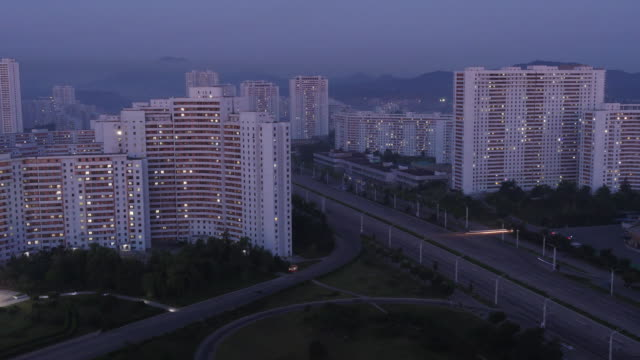 amazing night to day time lapse of residential buildings and traffic on kwangbok st. - wide shot at night. pyongyang, north korea, dprk - spoonfilm stock videos and b-roll footage