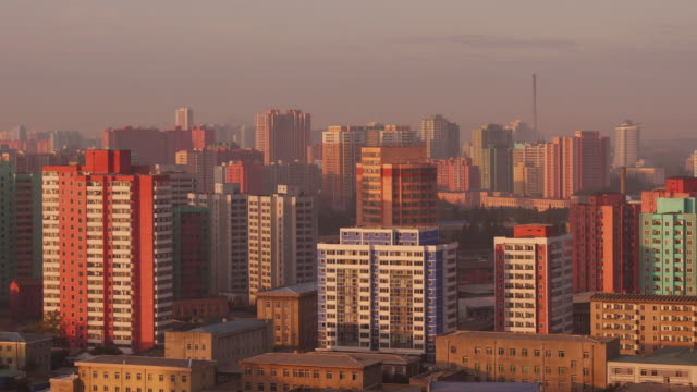 amazing night to day  time-lapse of colorful houses in the city center of pyongyang, north korea, drpk. wide shot from koryo hotel - spoonfilm stock videos and b-roll footage
