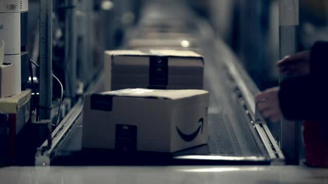 amazon agency workers 'put on zero hours contracts'; england: int various of boxes along conveyor belt in amazon warehouse - warehouse stock videos & royalty-free footage