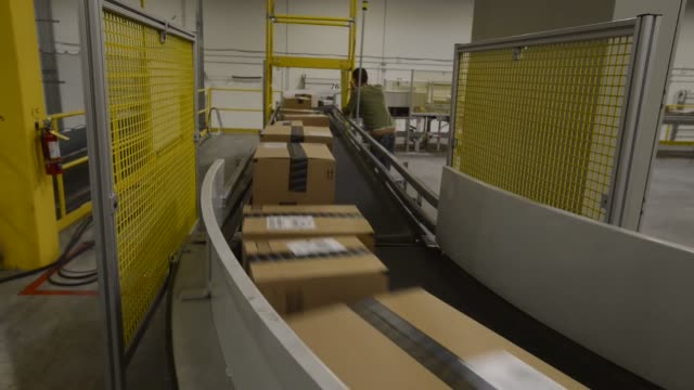 Amazon boxes and envelopes travel down a long convey belt through the Amazon fulfillment center while an employee controls the speed of their...