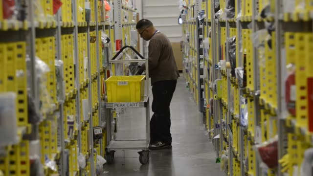 amazon employees push carts down rows and rows of stacked items and place them in a shopping cart for shipping amazon distribution center storage on... - push cart stock videos and b-roll footage