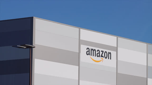 amazon logo featured on the exterior of the amazon warehouse in the paris region. amazon is an american e-commerce company based in seattle. it is... - gafam stock-videos und b-roll-filmmaterial