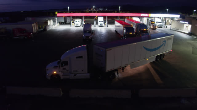 amazon prime truck pulling out of gas station at night - drone shot - refuelling stock videos & royalty-free footage