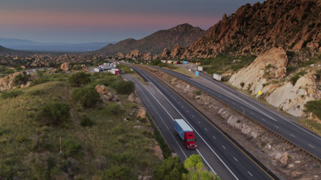 vídeos y material grabado en eventos de stock de amazon truck pulling into texas canyon rest area, az at dawn - drone shot - autopista