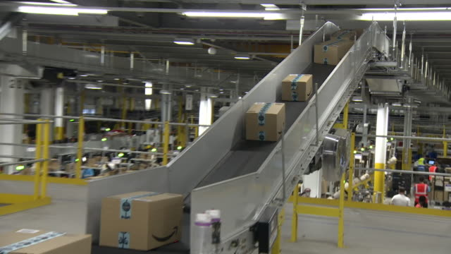 amazon warehouse in tilbury cardboard parcels moving along conveyor belt - employment issues stock videos & royalty-free footage