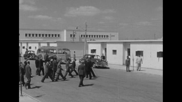 US Ambassador Jefferson Caffery entourage exit factory cross wide street to waiting motorcade vehicles / WS mosque with minaret / Caffery Egyptian...